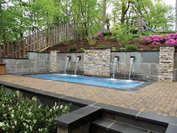 A small space fiberglass pool installation aqua magazine for Pool design for sloped yard