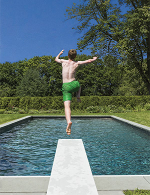 photo of a boy jumping off of a diving board