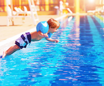 photo of a child jumping in a swimming pool