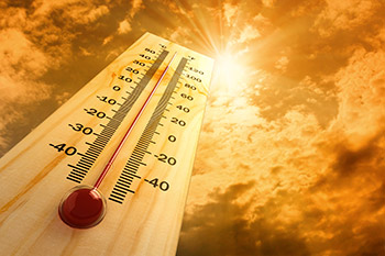 photo of a thermometer under a sunny sky
