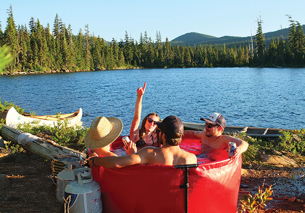 photo of people in a backcountry hot tub by a lake