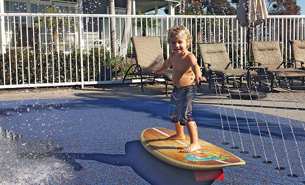 photo of a little boy playing in a splash pad