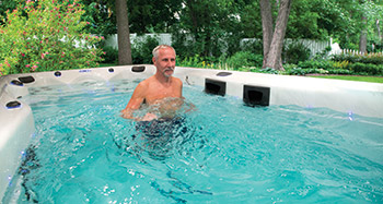 photo of a man using a Master Spas swim spa