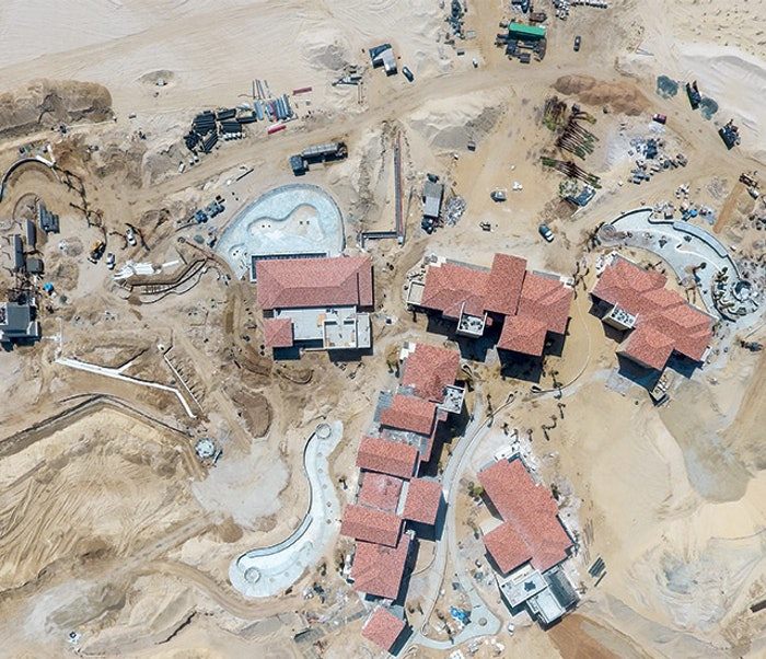 Aerial view of pool and lagoon construction. Note the depots of supplies stacked in the sand, including palm trees and pipe, along with active heavy hydraulic equipment (material handler, backhoe and wheel dozer).