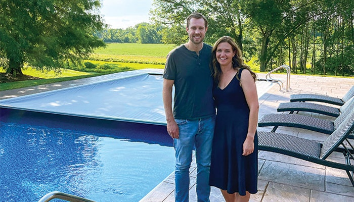 Pat and Sarah Barrett stand in front of their automatic pool cover that saved the life of a woman who safely drove over it after losing control of her car. (Photos courtesy Brad Lovins)